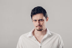 Handsome young frustrated and resentful man in white shirt on gray background. soft, light. Handsome young frustrated and resentful brunette man in white shirt Stock Photos