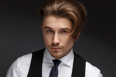 Handsome young gentelman wearing elegant white shirt  and black suit posing on camera. Stock Photo