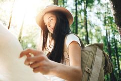 Handsome young girl traveling among trees in forest at sunset. Woman wearing backpack and hat hold in hands location map Royalty Free Stock Image