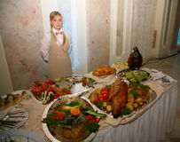 A handsome young girl waiter presents an impressive buffet in a Russian restaurant. Stock Photos