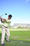 Handsome young golfer in action. A golfer in action on a practice range, hitting the ball with a club Stock Photos