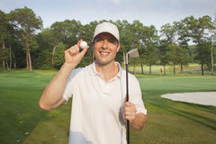 Handsome young golfer holds club and ball on a course Stock Photo