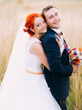 Handsome young groom and beautiful redhair bride posing outdoor, enjoying marriage day together Stock Photo