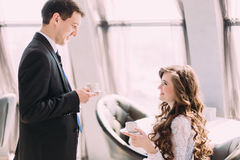 Handsome young groom in black suit brings his bride coffee Stock Image