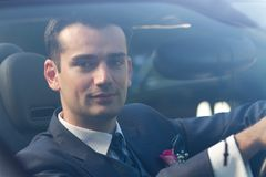 Handsome young groom in a car Royalty Free Stock Images