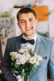 Handsome young groom holding wedding bouquet of white roses Stock Image