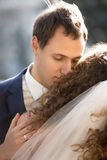 Handsome young groom hugging bride tenderly Stock Photography