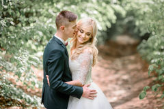Handsome young groom kisses bride tenderly Stock Photo