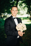 Handsome young groom posing outside in nature Royalty Free Stock Photography