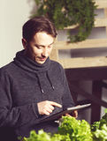 Handsome modern grower using his tablet while growing plants ind Stock Photos
