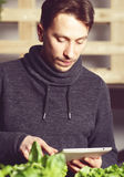 Handsome modern grower using his tablet while growing plants ind Stock Photo