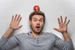 Handsome young guy balancing red apple on his head. Stock Photos