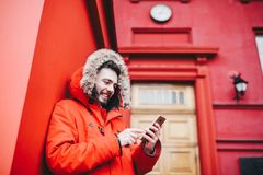 A handsome young guy with beard and red jacket in hood a student uses a mobile phone, writes, writes a correspondence over the pho stock photography
