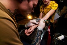 Handsome young guy in a black hat and with tattoos, beats a tattoo on his arm, tattoo salon. Tattoo artist royalty free stock photos