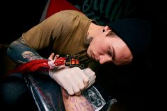Handsome young guy in a black hat and with tattoos, beats a tattoo on his arm, tattoo salon. Tattoo artist royalty free stock images