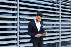 Handsome young guy businessman holds, uses tablet stands near wa Stock Image