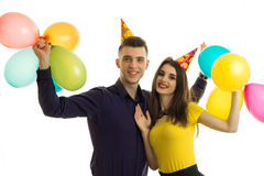 Handsome young guy and cute smiling girl celebrating her birthday and raise up balloons Royalty Free Stock Photo