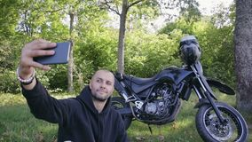 Male biker traveler takes a selfie photo on the background of his motorcycle. A handsome, young guy in a dark jacket photographs himself against a black stock video footage