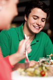 Handsome young guy enjoying meal in restaurant Stock Photos