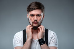 Handsome young guy is expressing his masculinity. Attractive man is touching his beard confidently. He is looking at camera with boastfulness. Isolated on grey Stock Photos