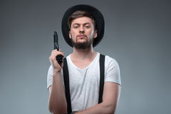 Handsome young guy with gun and hat Royalty Free Stock Photography