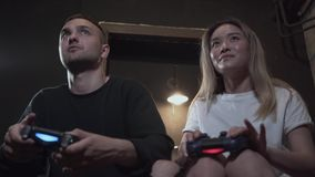 Portrait handsome young guy with his girlfrend having fun playing video games with excellent mood in modern loft club stock video