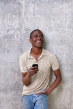 Handsome young guy laughing with mobile phone. Portrait of handsome young guy laughing with mobile phone Stock Image