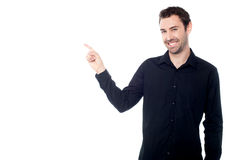 Handsome young guy pointing at something Stock Photo