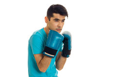 Handsome young guy practicing boxing in blue gloves isolated on white background Stock Photography