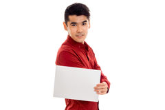 Handsome young guy in red t-shirt with empty placard looking at the camera isolated on white background Royalty Free Stock Photography