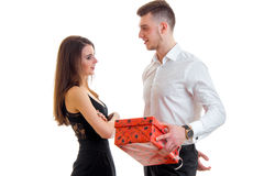 Handsome young guy in shirt standing next to the charming girl and gives her a gift Royalty Free Stock Image