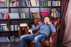 Handsome Young Guy Sitting on the Library Chair Stock Image