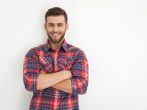 Handsome young guy standing against white wall. Stock Images