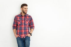 Handsome young guy standing against white wall. Royalty Free Stock Images