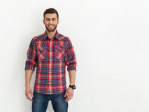 Handsome young guy standing against white wall. Stock Photography