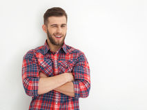 Handsome young guy standing against white wall. Royalty Free Stock Photography