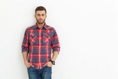 Handsome young guy standing against white wall. Stock Photos
