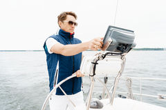 Handsome, young guy standing at a steering wheel on a yacht. Tra Royalty Free Stock Photos
