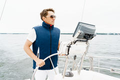 Handsome, young guy standing at a steering wheel on a yacht. Tra Royalty Free Stock Photography