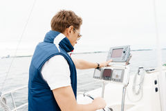 Handsome, young guy standing at a steering wheel on a yacht. Tra Stock Photo