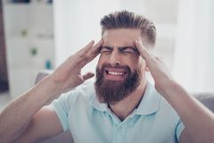 Handsome young guy is suffering from strong headache. He is hold stock photo