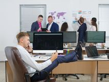 Handsome young guy in suit talking on mobile phone, sitting in office with feet on the desktop. Close-up of a men sitting in the office with his feet on the Royalty Free Stock Image