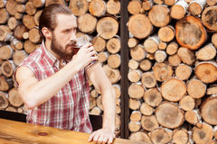 Handsome young guy is swigging lager in pub Royalty Free Stock Photography