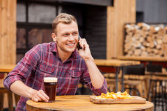 Handsome young guy is using telephone in bar Stock Photos