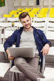 Handsome young guy is waiting for lecture. Attractive man is sitting in auditory hall and holding a laptop. He is looking forward and flirting with someone. The Stock Photography