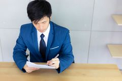 Handsome young guy is writing and reading resume and documents f stock image