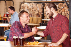Handsome young guys are meeting in beerhouse Stock Photography