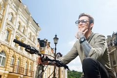 Handsome young hipster guy is cycling on street Stock Photo