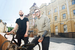 Handsome young hipster guys are cycling in city Royalty Free Stock Photo