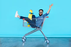 Handsome young hipster man sitting in the shopping cart stock images